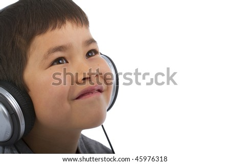 Cute young boy listening to music and smiling