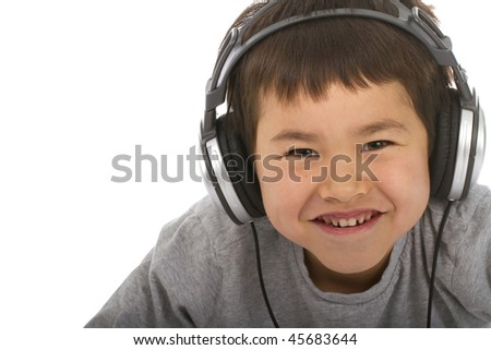 Cute young boy listening to music and smiling, isolated on white background