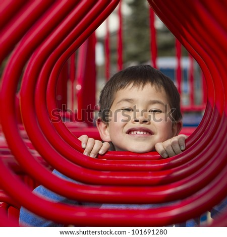 Cute young boy looking through the hoops of a playground structure - stock photo