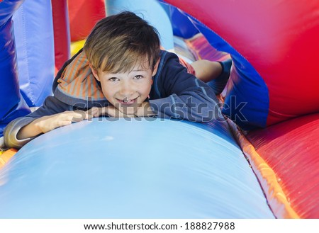Cute young boy lying down on a bouncy castle - stock photo