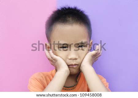 Cute young boy making a funny face on two colors background - stock photo