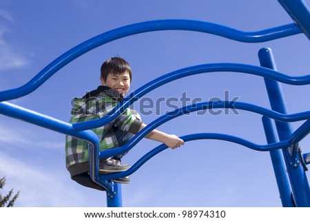 Cute young boy playing on playground equipment - stock photo