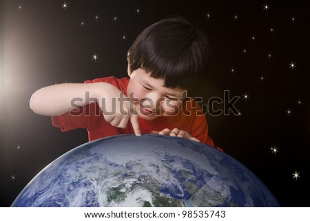 Cute young boy pointing to a spot on planet earth with space background and stars. Elements of this image furnished by NASA.