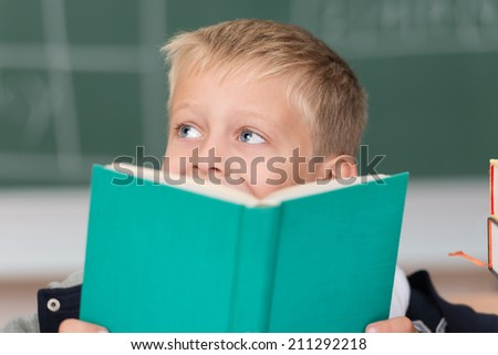 Cute young boy reading in class with the textbook hiding part of his face and his eyes visible as he looks to the side for guidance - stock photo