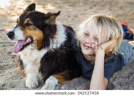 Cute  young boy relaxing with arm around pet dog at beach - stock photo