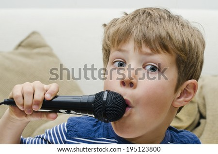 Cute young boy singing into a microphone - stock photo