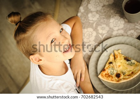 Cute young boy sitting indoor in the cafe or restaurant near the table and eating big tasty piece of pizza. He smile, laugh and enjoy his meal. Top-knot hairstyle. Close up. Top view shooting point?.