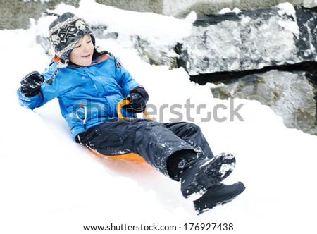 Cute young boy sledging down a hill  - stock photo