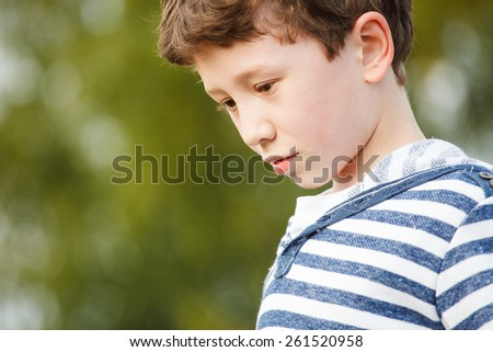Cute young boy staying on the field  - stock photo