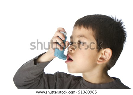 Cute young boy using his asthma inhaler isolated on white background