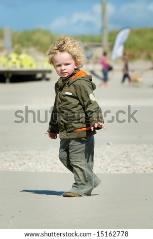 cute young boy walking on the beach - stock photo