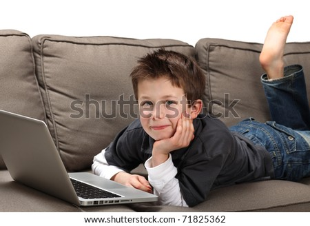 cute young boy with a laptop on a couch - stock photo