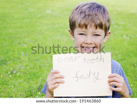 Cute young boy with a missing tooth holding a sign for the tooth fairy - stock photo