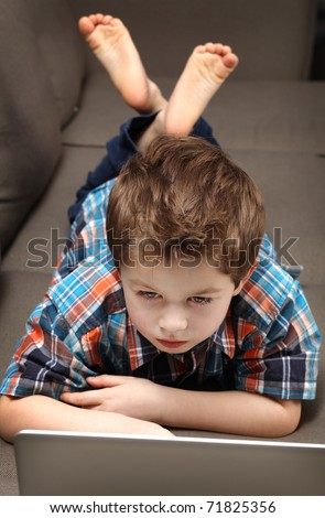 cute young boy with laptop on a couch - stock photo
