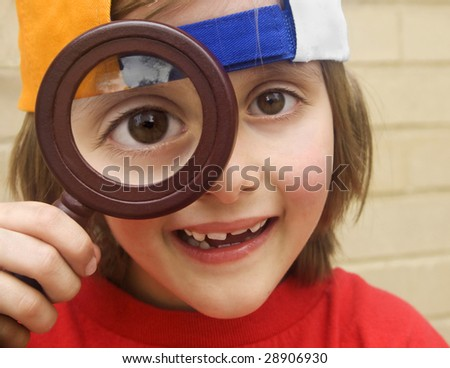 cute young boy with magnifying glass - stock photo