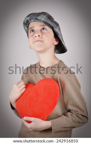 Cute young boy with newsboy cap holding a plush red heart and looking up on Valentines day - stock photo