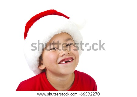 Cute young boy with two front teeth missing wearing a Christmas Santa hat isolated on white background