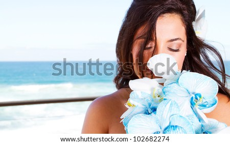 cute young bride smelling bouquet - stock photo