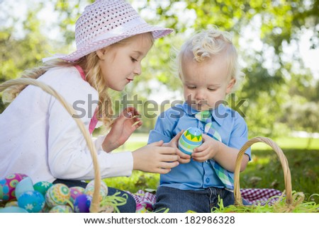 Cute Young Brother and Sister Enjoying Their Easter Eggs Outside in the Park Together. - stock photo