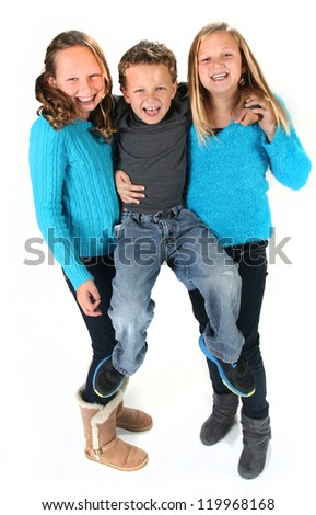 Cute young brother with older sisters isolated on white background - stock photo
