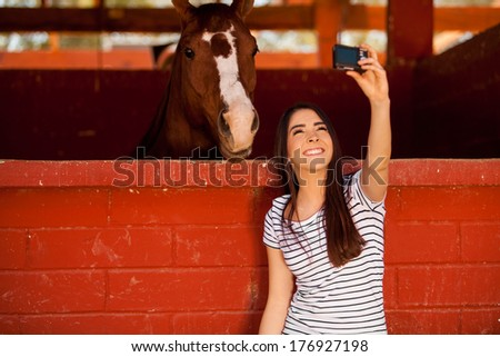 Cute young brunette taking a selfie with his horse in the stables - stock photo