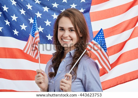Cute young brunette woman celebrating National Independence Day on 4th of July in United States of America. Attractive model with toothy smile and flag on the background