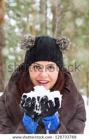 Cute young brunette woman playing with snow  outdoors - stock photo