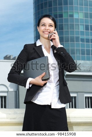 Cute young business lady talking mobile phone and holding laptop in hand against modern office building - stock photo