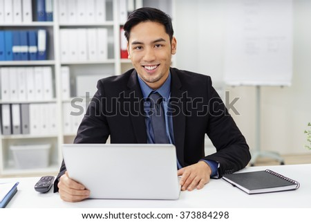 Cute young businessman with goatee looking ahead from behind laptop at desk in office with happy expression - stock photo