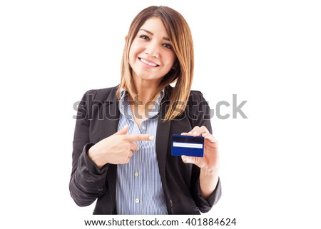 Cute young businesswoman holding a credit card and pointing at it on a white background
