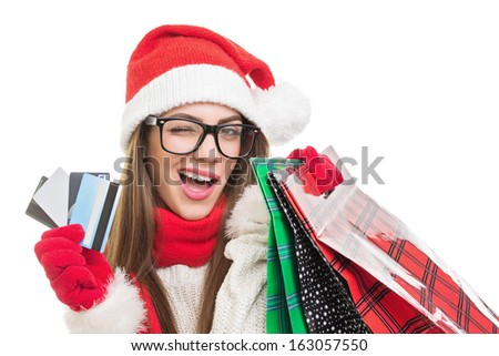 Cute young Caucasian brunette woman holding credit cards and shopping bags wearing winter clothes, black nerd glasses and Santa Claus beanie hat. Christmas shopping concept. - stock photo