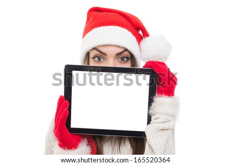 Cute young Caucasian girl wearing Santa beanie hat and red gloves hiding behind tablet computer with blank screen. Copy space available on the tablet screen and in the background. - stock photo