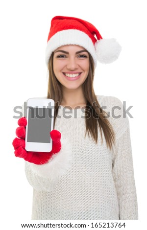 Cute young Caucasian girl with Santa hat showing  smart phone screen smiling looking at camera isolated on white background. Copy space available on mobile screen. - stock photo