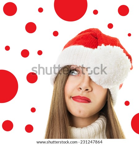 Cute young Caucasian woman with Christmas hat looking up. Beautiful teenage blue eyed girl with brown hair wearing red lipstick and knitted Santa hat. - stock photo