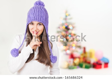 Cute young Caucasian woman with purple beanie hat smiling gesturing hush looking at camera with colorful decorated Christmas tree and presents blurred in the background. - stock photo