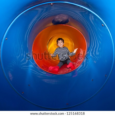 Cute young child boy playing in tunnel on playground