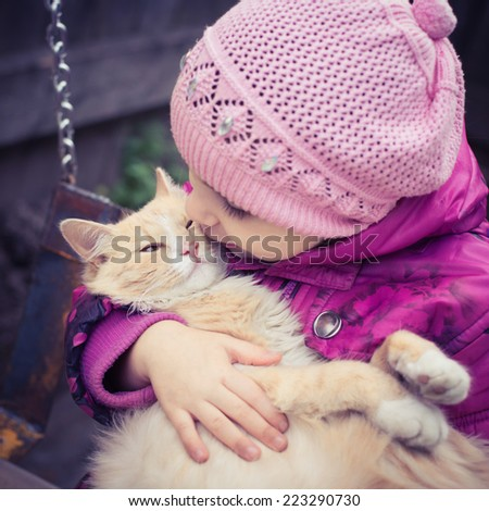 Cute young child holding kitten.