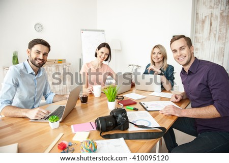 Cute young colleagues are working in cooperation - stock photo
