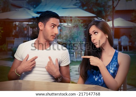 Cute Young Couple Arguing - Young adult couple arguing with funny expressions and gestures, out on a date   - stock photo