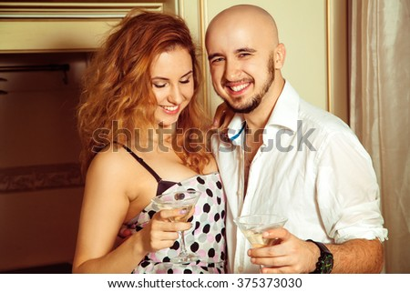 Cute young couple at martini home party. Celebrate, disco, party, nightlife, entertainment, friendship concept. - stock photo