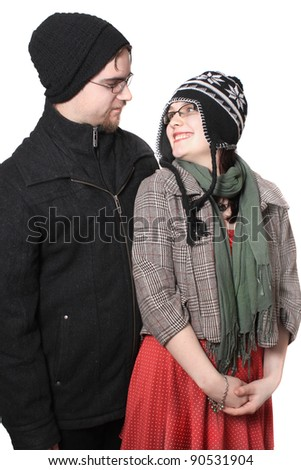 Cute young couple happy together dressed in winter clothing on a white background