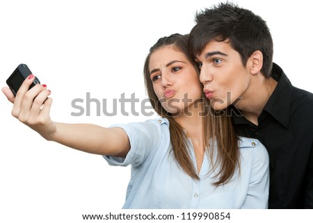 Cute young couple having fun taking self portrait.Isolated on white. - stock photo