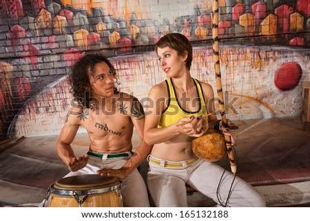 Cute young couple in capoeira outfit playing traditional instruments - stock photo