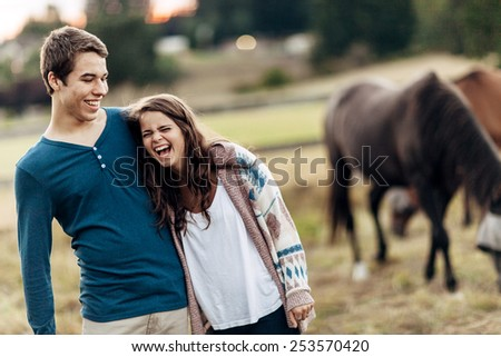 Cute Young Couple in Field near Horses - stock photo