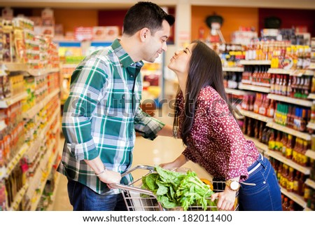 Cute young couple kissing each other across a shopping cart at the supermarket - stock photo
