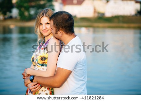Cute young couple lovely embracing and looking at camera at water background in sunny day, Copy space - stock photo