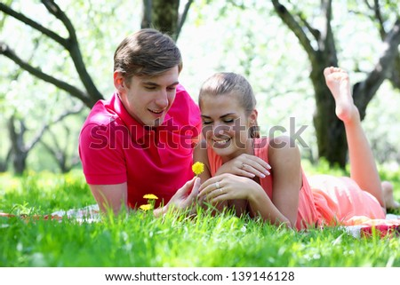 Cute young couple lying in a park - stock photo