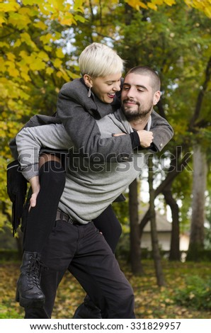Cute young couple piggyback in park at fall. Selective focus on the guys face