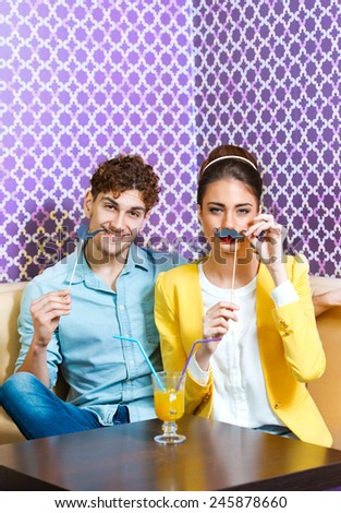 Cute young couple sitting at the table having fun  - stock photo