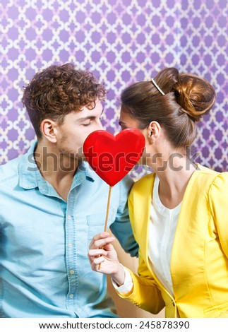 Cute young couple sitting at the table kissing behind a heart - stock photo